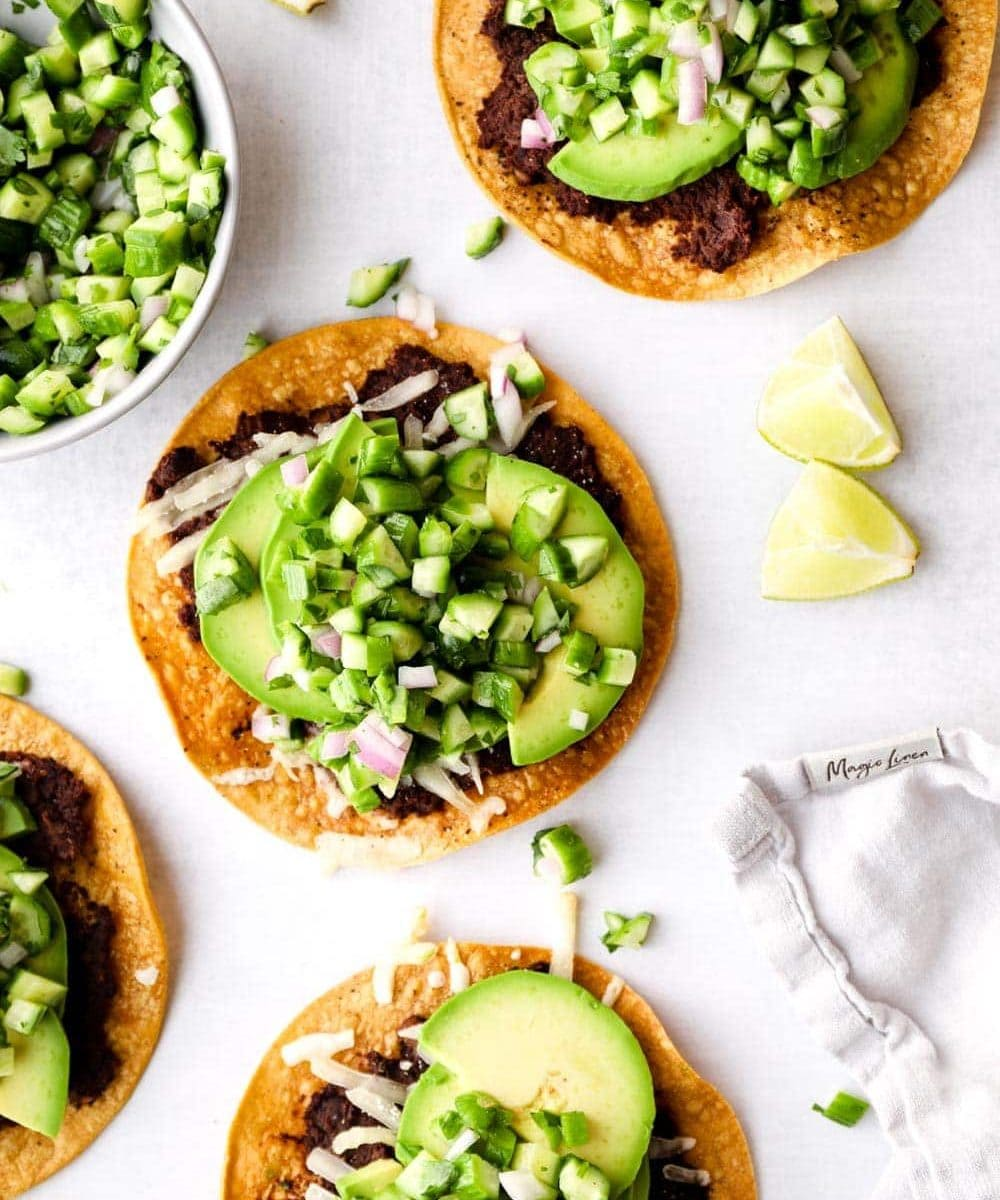 Avocado Tostadas with lime wedges on a grey surface.