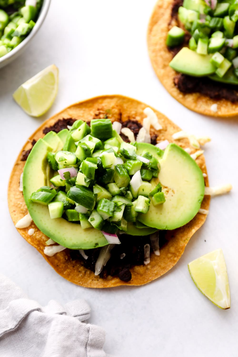 Avocado Tostada with vegan cheese, refried beans, and cucumber pico.