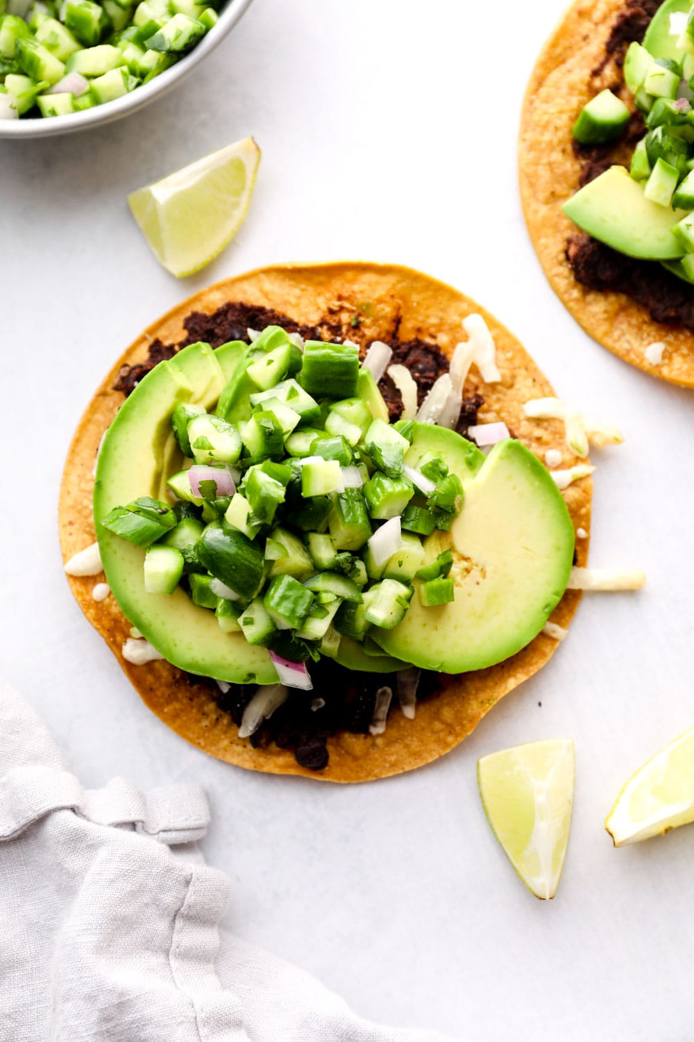 An avocado tostada with beans and cucumber pico on a grey background.