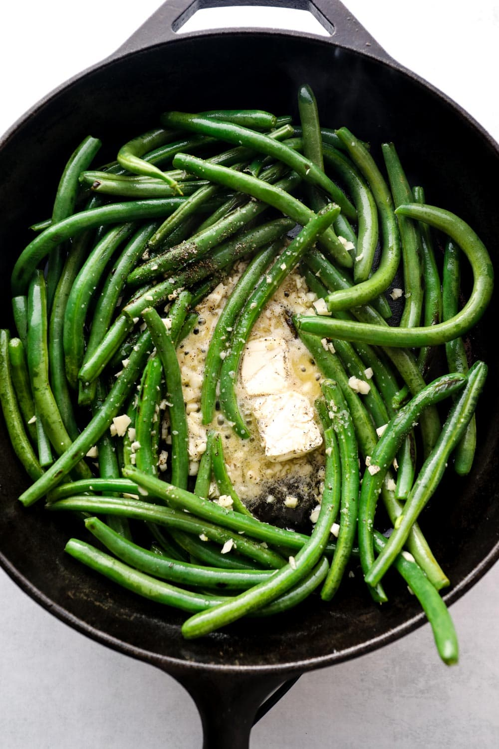 Green beans cooking in a cast iron skillet with butter, salt, and pepper.