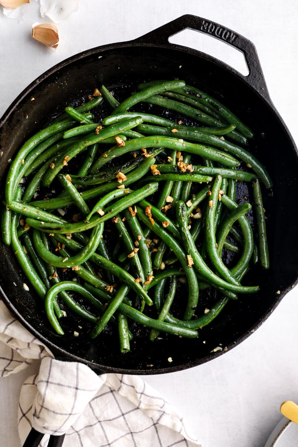 Green beans and garlic in a cast iron skillet.