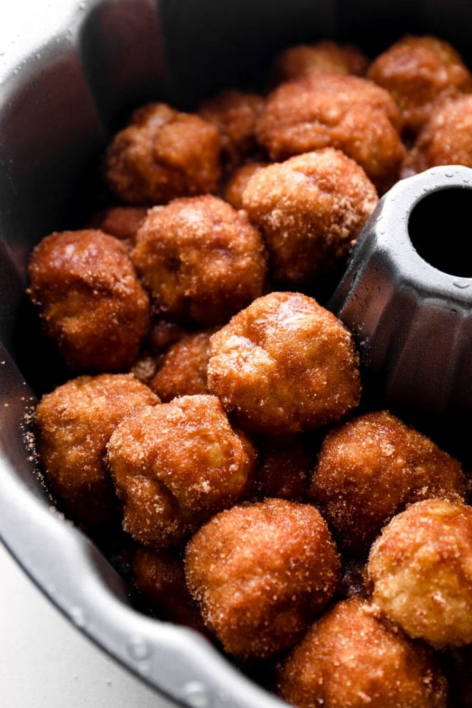 Homemade gluten free dough balls rolled in cinnamon sugar in a bunt pan.