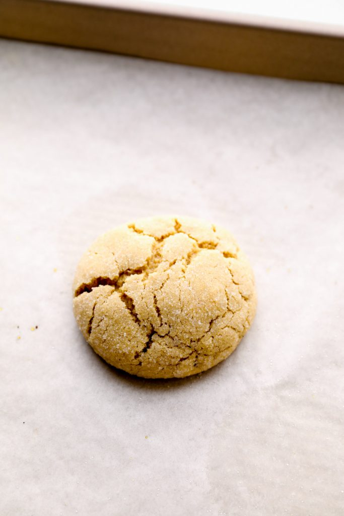 A baked peanut butter cookie waiting to be pressed with a chocolate kiss.