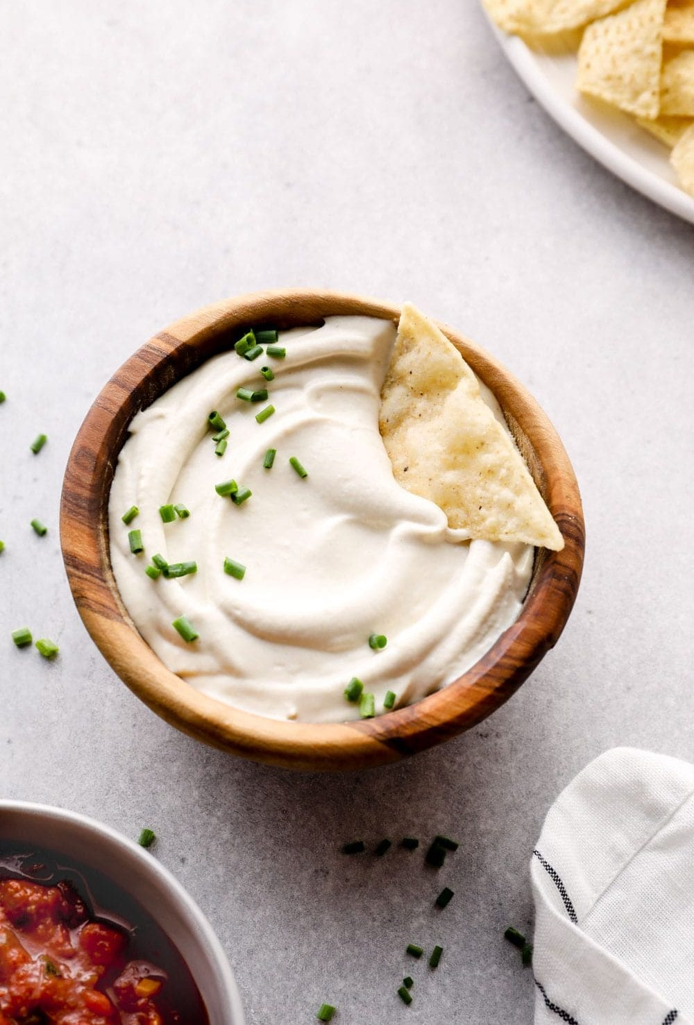 Cashew Sour Cream in a bowl garnished with chives.