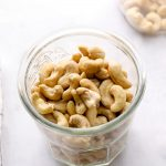 Raw cashews in a jar on a grey background.