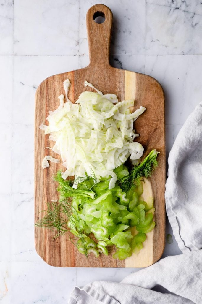 Shaved fennel and celery on a cutting board.