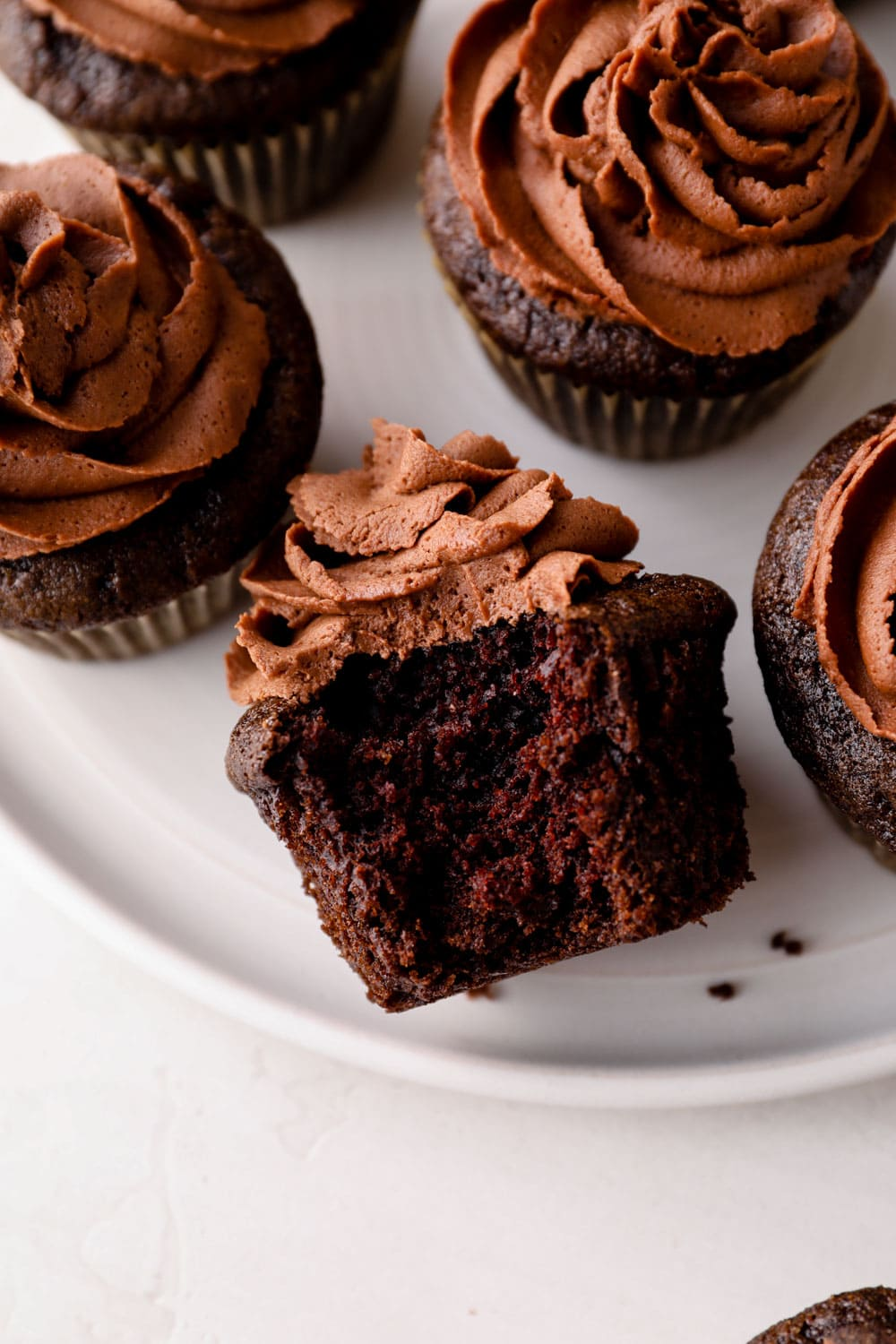 A bite out of a chocolate cupcake with chocolate frosting.