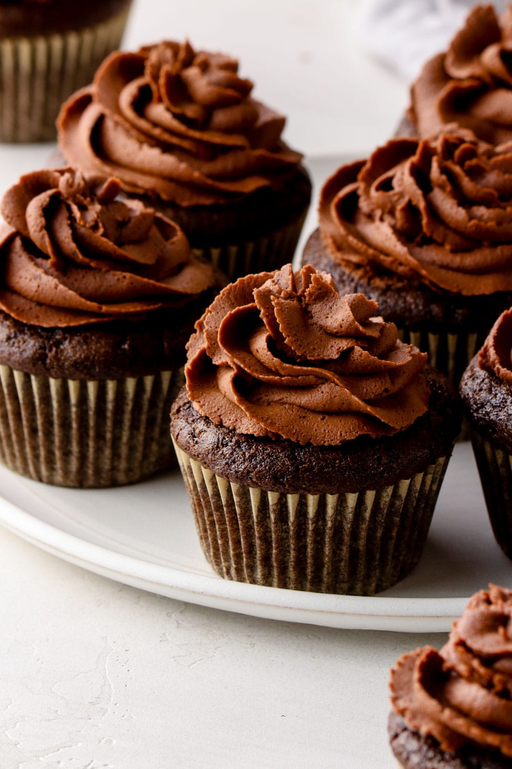 Frosted gluten free chocolate cupcakes on a plate.