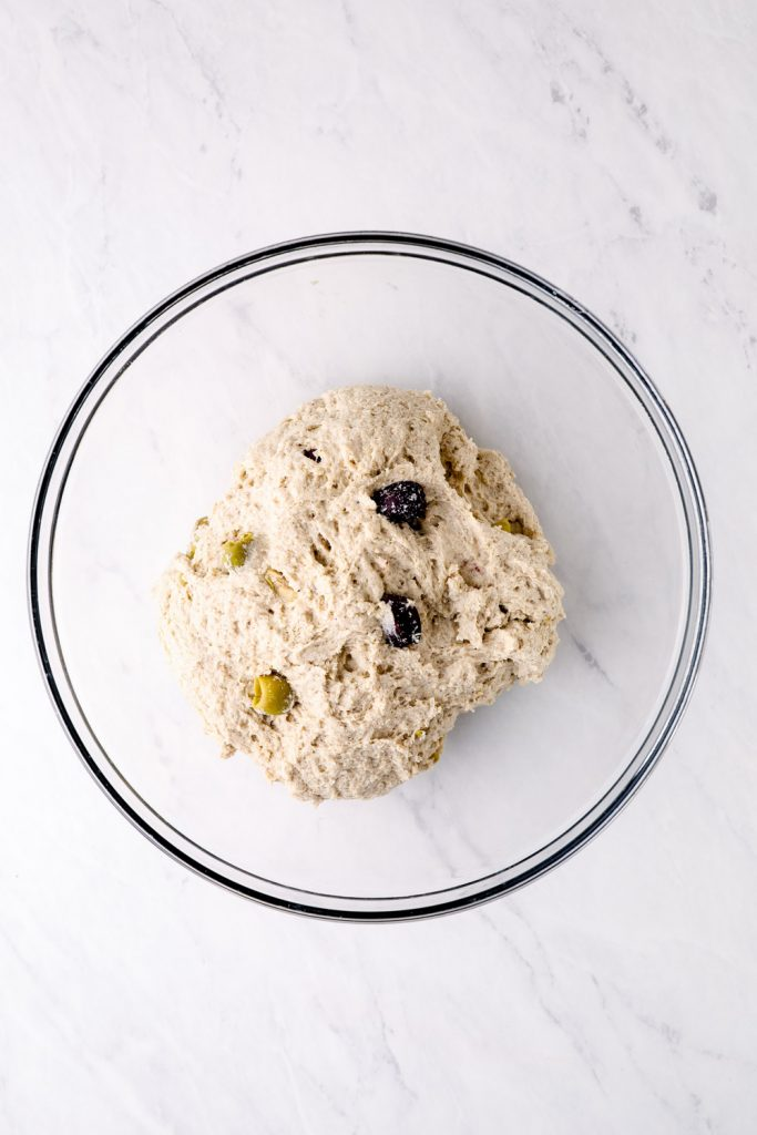 Gluten free olive bread rising in a glass bowl.