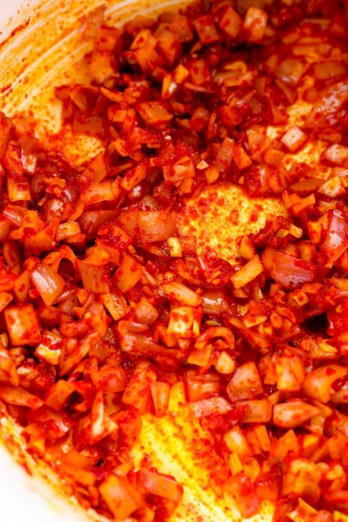 Sautéed shallot, garlic, and gochugaru in a pot.