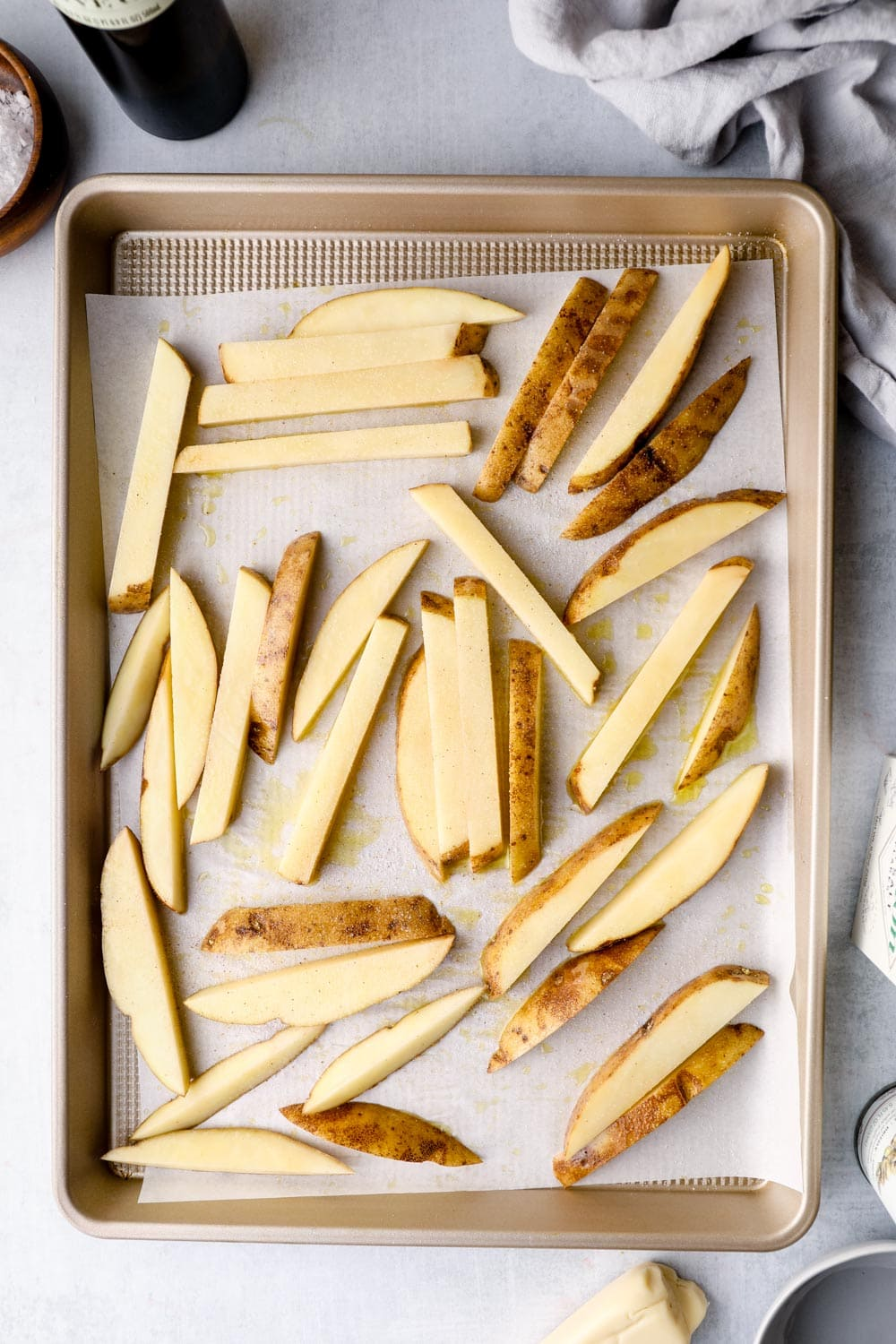 Potatoes cut into fries on a sheet pan with oil and salt.