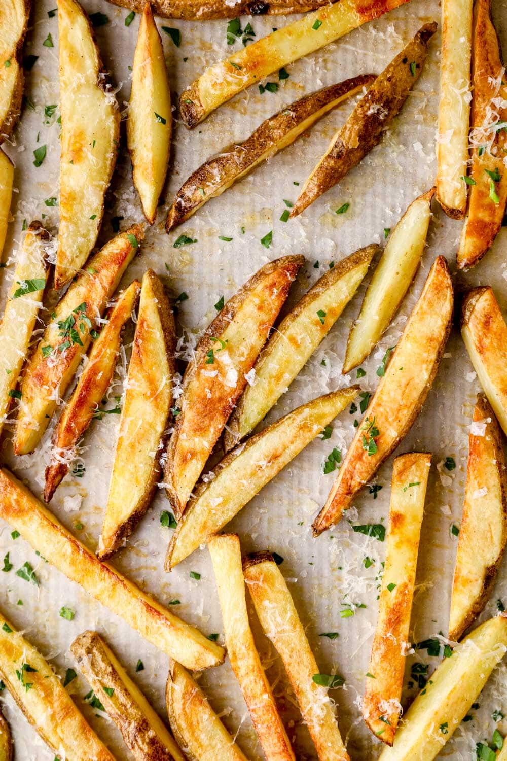 Baked truffle fries on parchment paper with grated parmesan cheese.