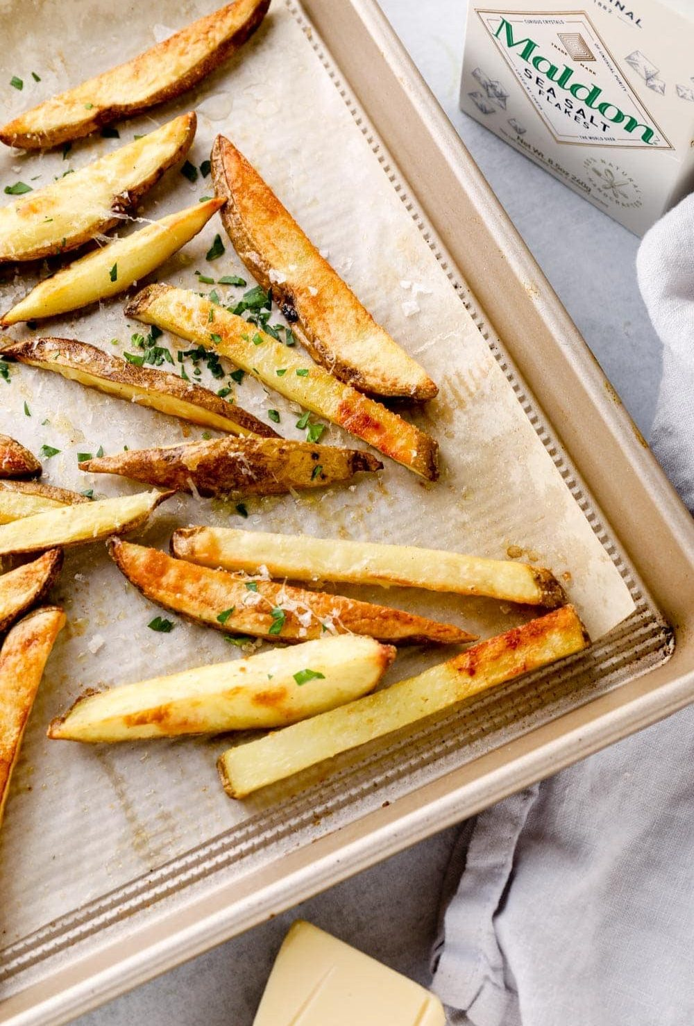Truffle fries on a sheet pan with flaky maldon salt.