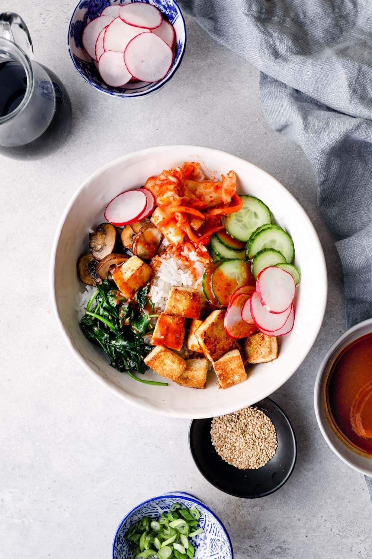 Vegan bibimbap bowl surrounded by toppings.