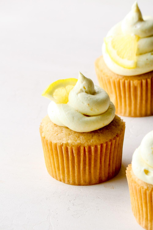 Vegan lemon buttercream swirled onto a vanilla cupcake with a wedge of lemon.