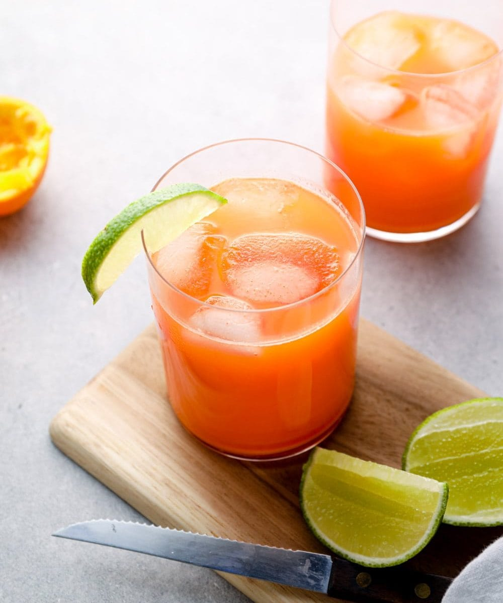 Carrot orange juice in a glass with lime.