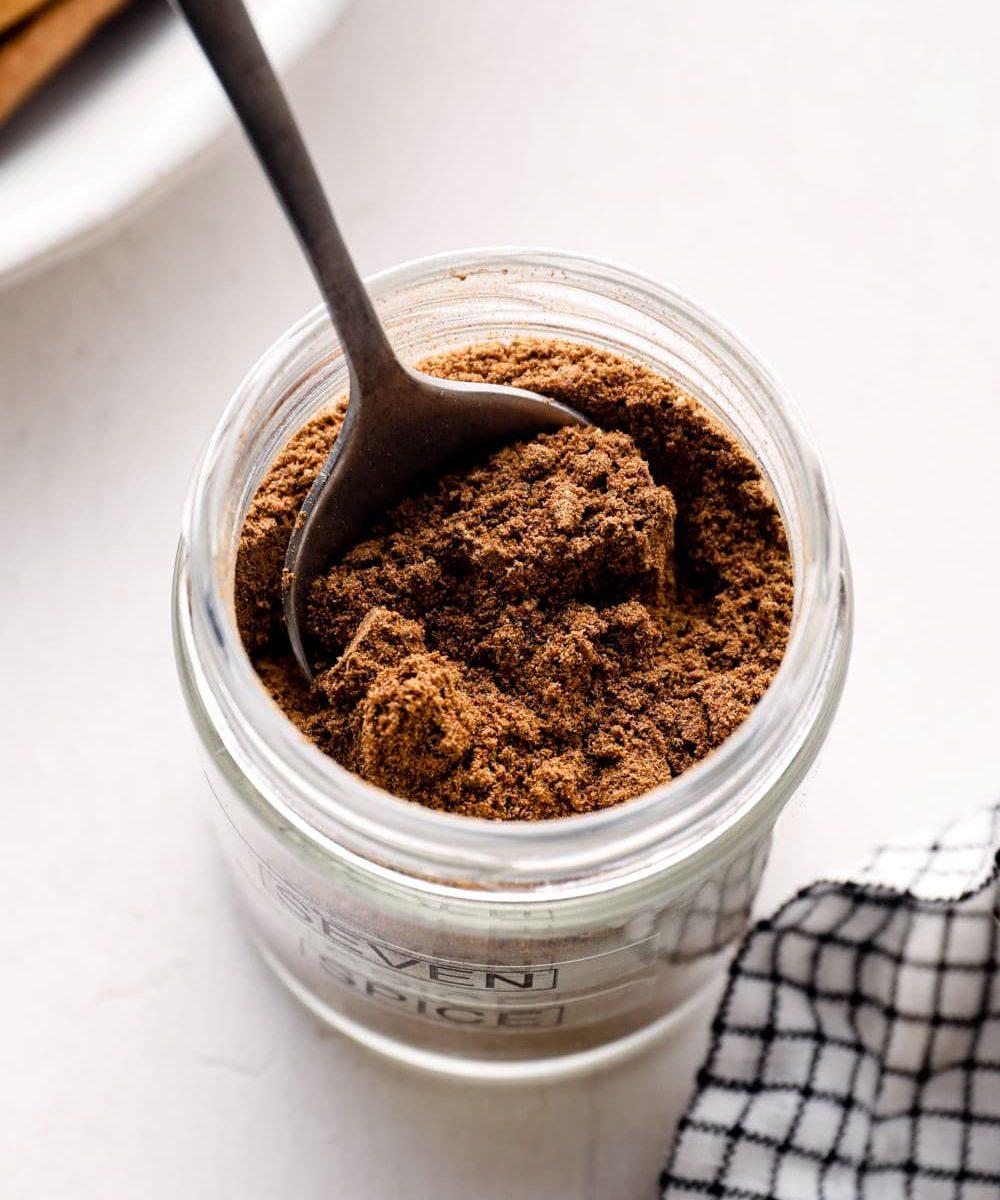 A spoon in a jar of Lebanese seven spice.