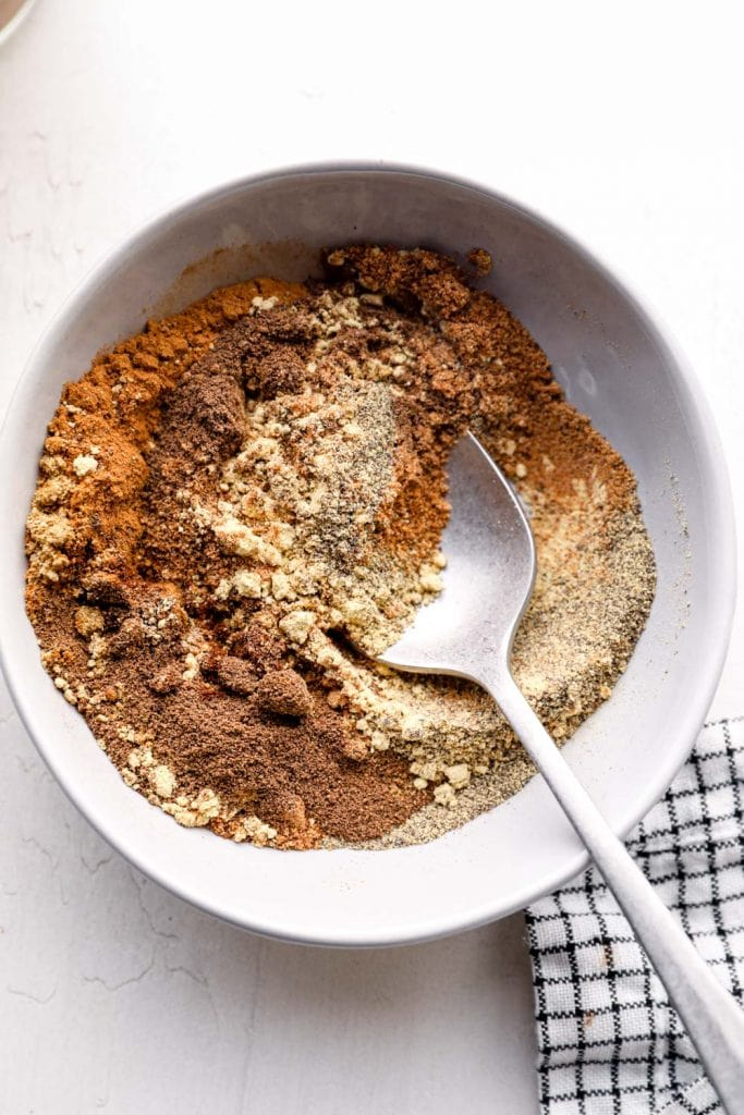 Seven spice being stirred together in a bowl.
