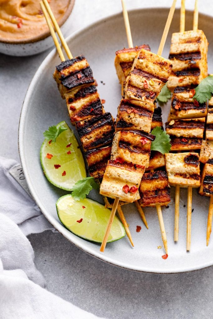 Tofu satay with lime and chili on a plate.