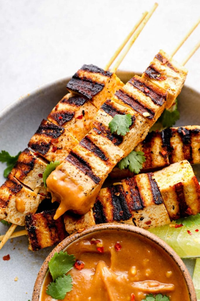 A grilled tofu skewer dipped in peanut sauce.