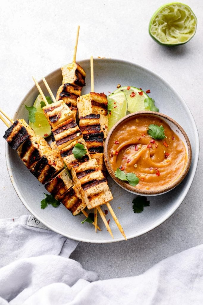 A plate of tofu satay skewers and peanut sauce.