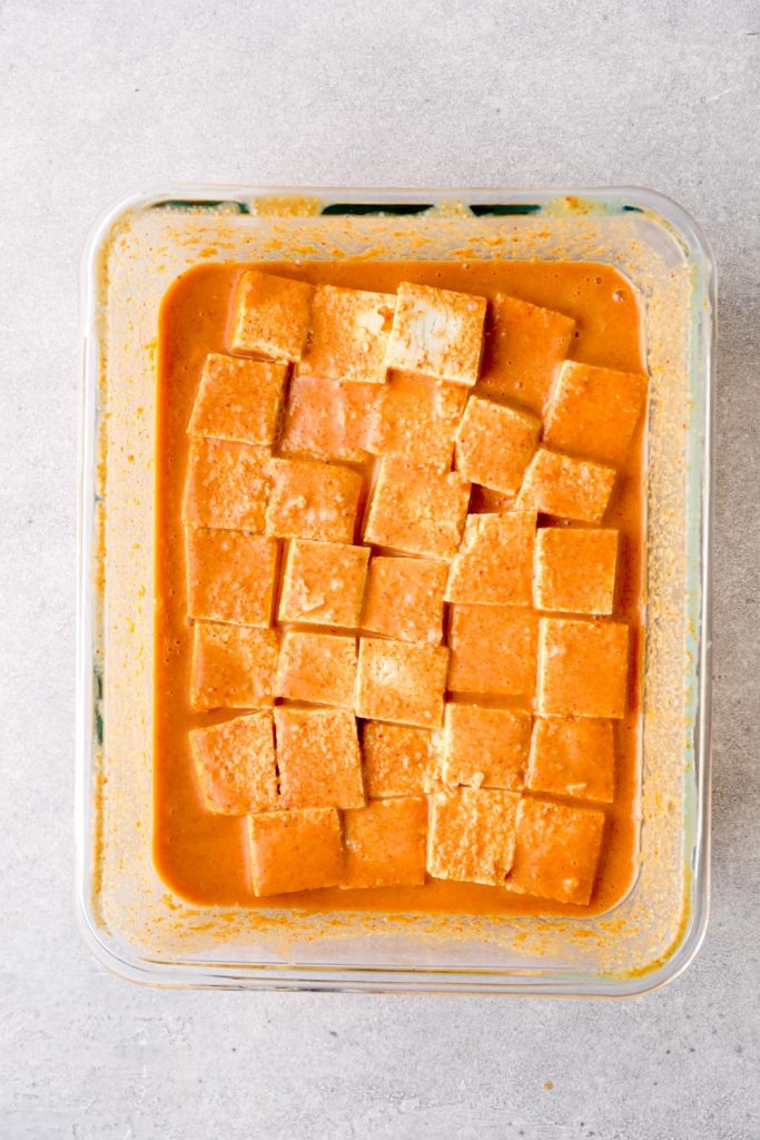Tofu cubes marinating in satay sauce.
