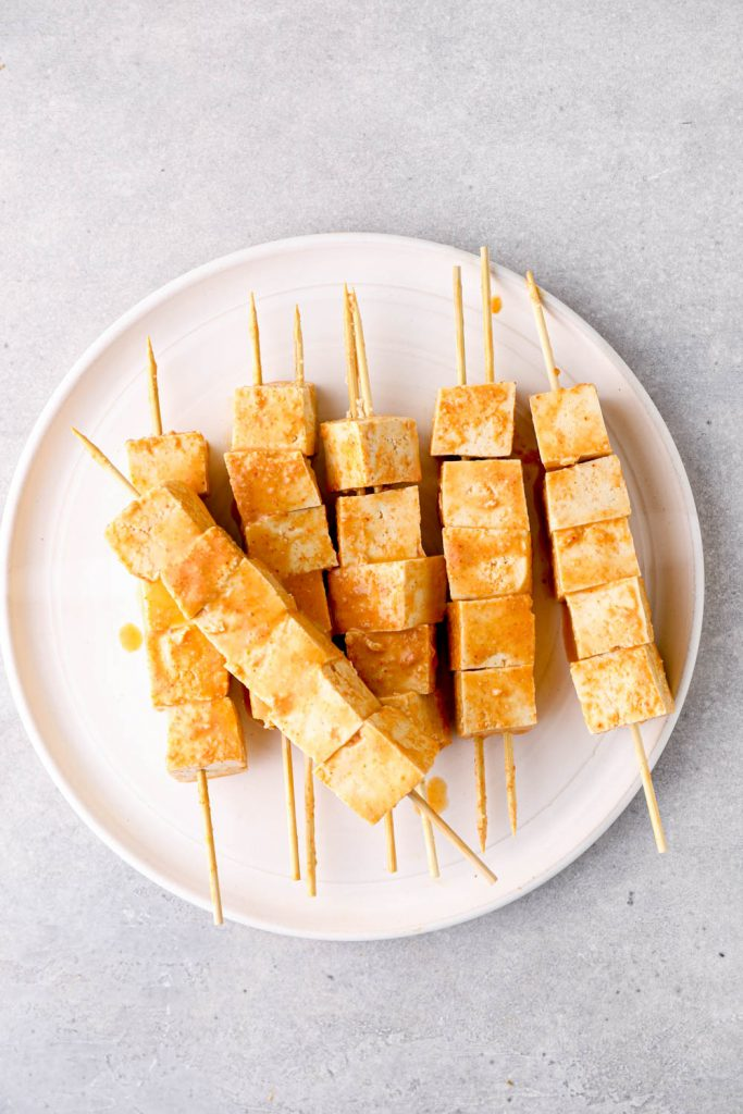 Marinated tofu on bamboo skewers.