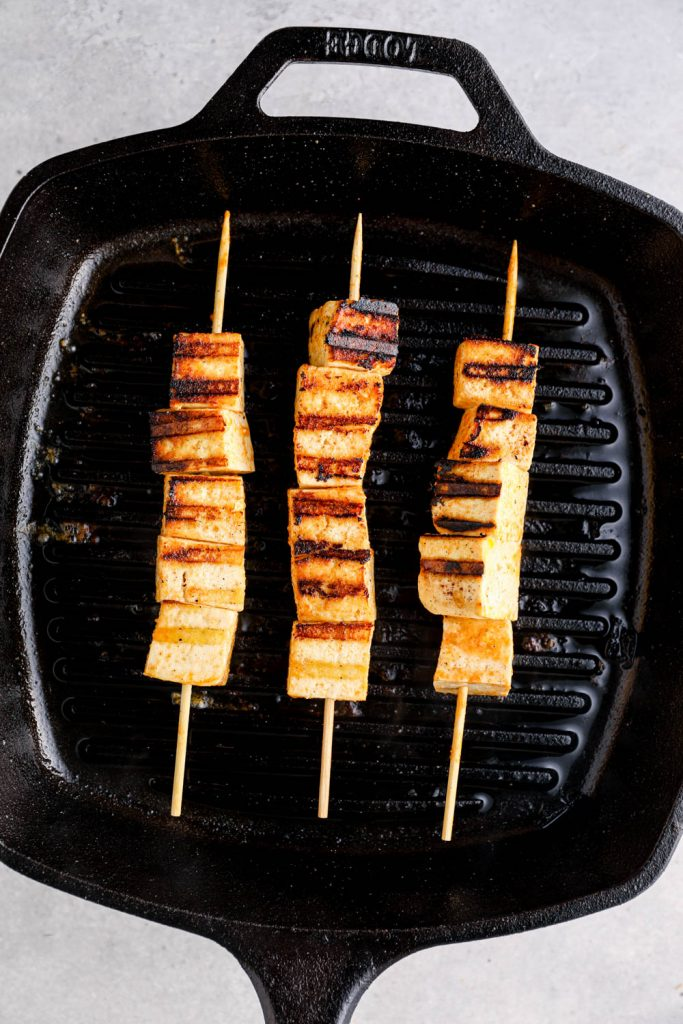 Tofu satay cooking on a grill pan.