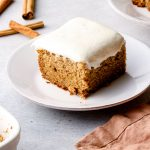 A slice of banana cake with dairy free cream cheese frosting.
