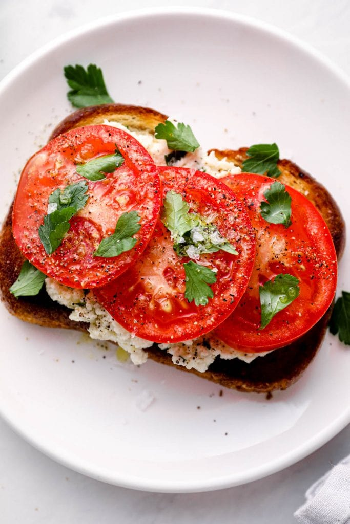 Ricotta toast with tomatoes, herbs, and olive oil.