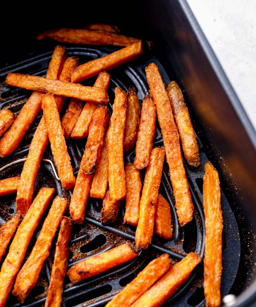 Air fryer frozen sweet potato fries in the air fryer basket.