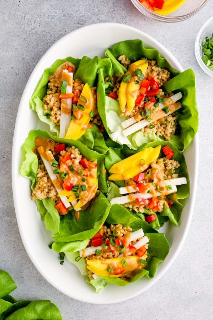 A white platter filled with Thai peanut lettuce wraps.