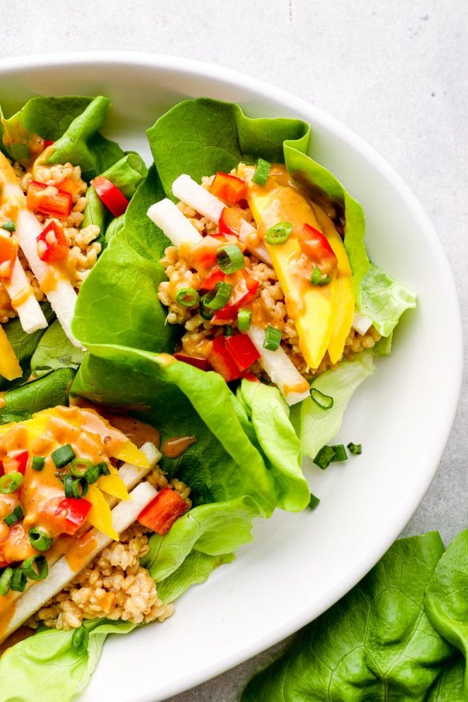 A Thai peanut lettuce wrap with colorful vegetables and herbs.