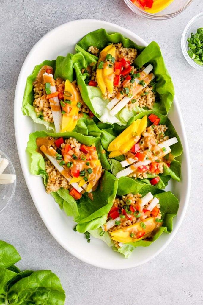 Thai lettuce wraps arranged on a white platter.