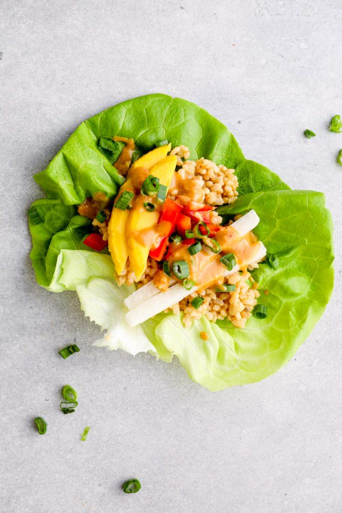 Butter lettuce filled with peanut sauce rice, vegetables, mango, and cilantro.