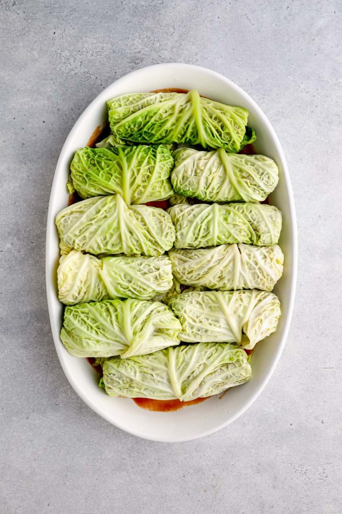 Rolled stuffed cabbage in a baking dish with tomato sauce.