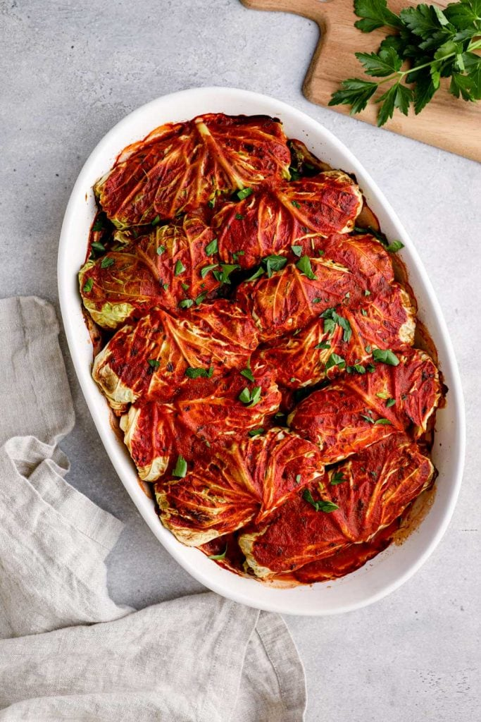 Baked vegetarian cabbage rolls in a white baking dish.