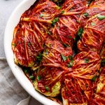 Baked vegetarian cabbage rolls with tomato sauce and parsley.