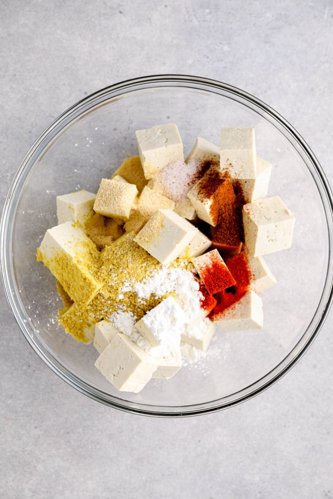 A bowl with tofu and seasonings.