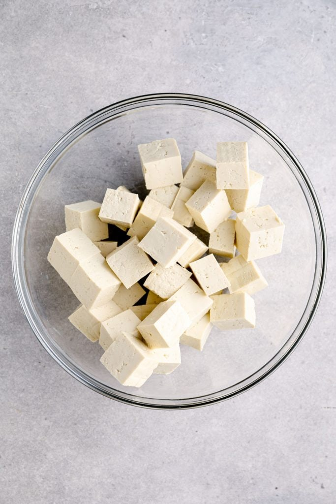 A glass bowl with cubed tofu.