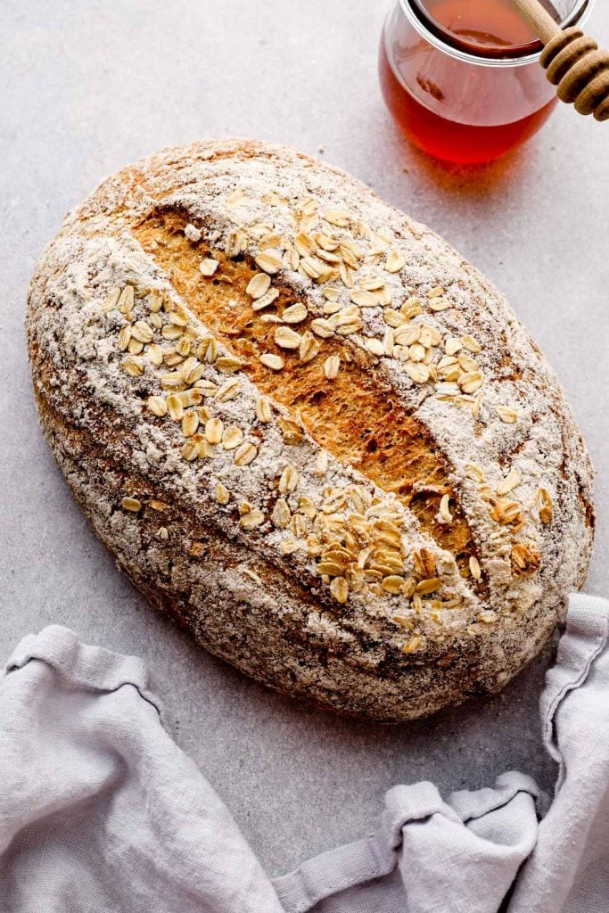 Baked gluten free bread with oats on a grey background.