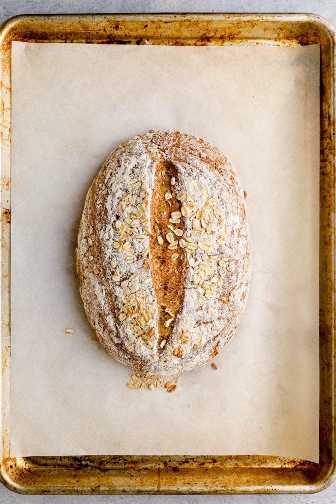 Baked gluten free honey oat bread on a sheet pan.