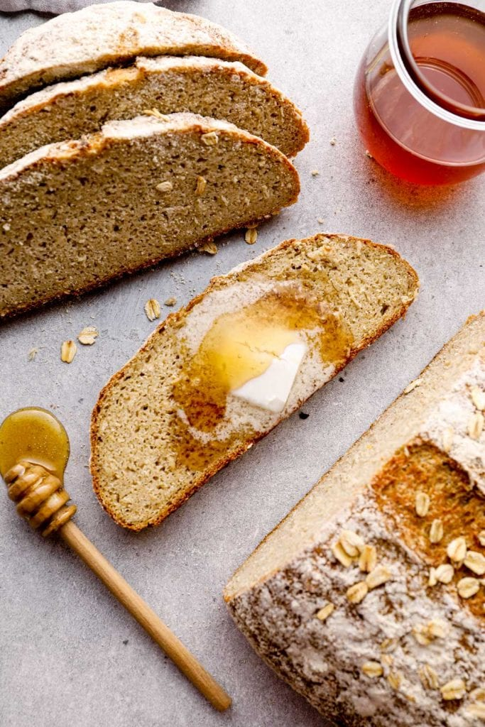 Sliced honey oat bread with butter.