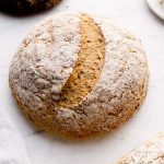 A loaf of artisan gluten free bread dusted with flour.