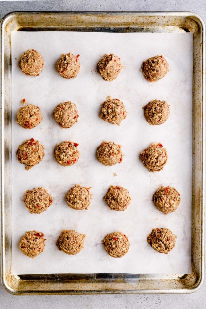 Raw lentil meatballs on a parchment lined baking sheet.