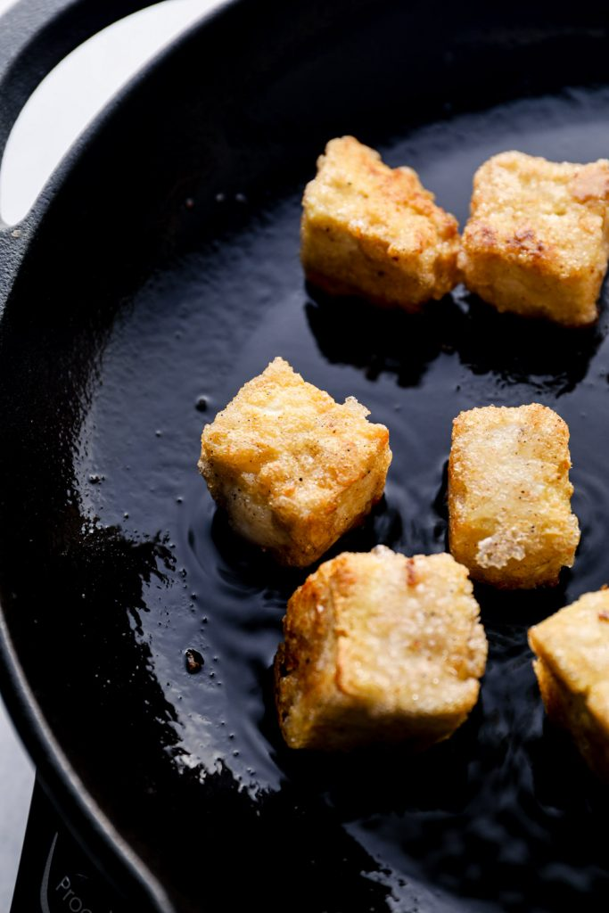 Salt and pepper tofu searing in a cast iron pan.