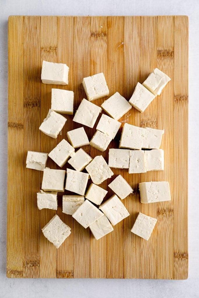 Cubed tofu on a cutting board.