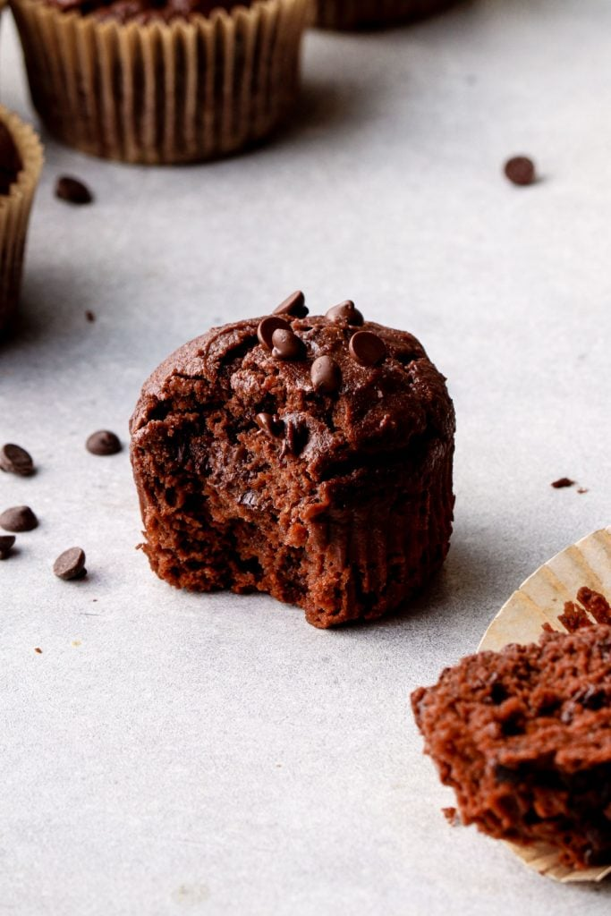 A chocolate sweet potato muffin with a bite out of it.