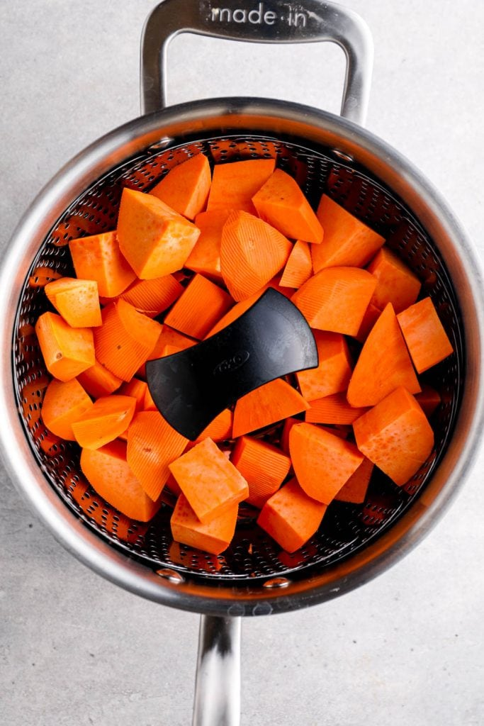Cubes of sweet potato in a steamer basket.