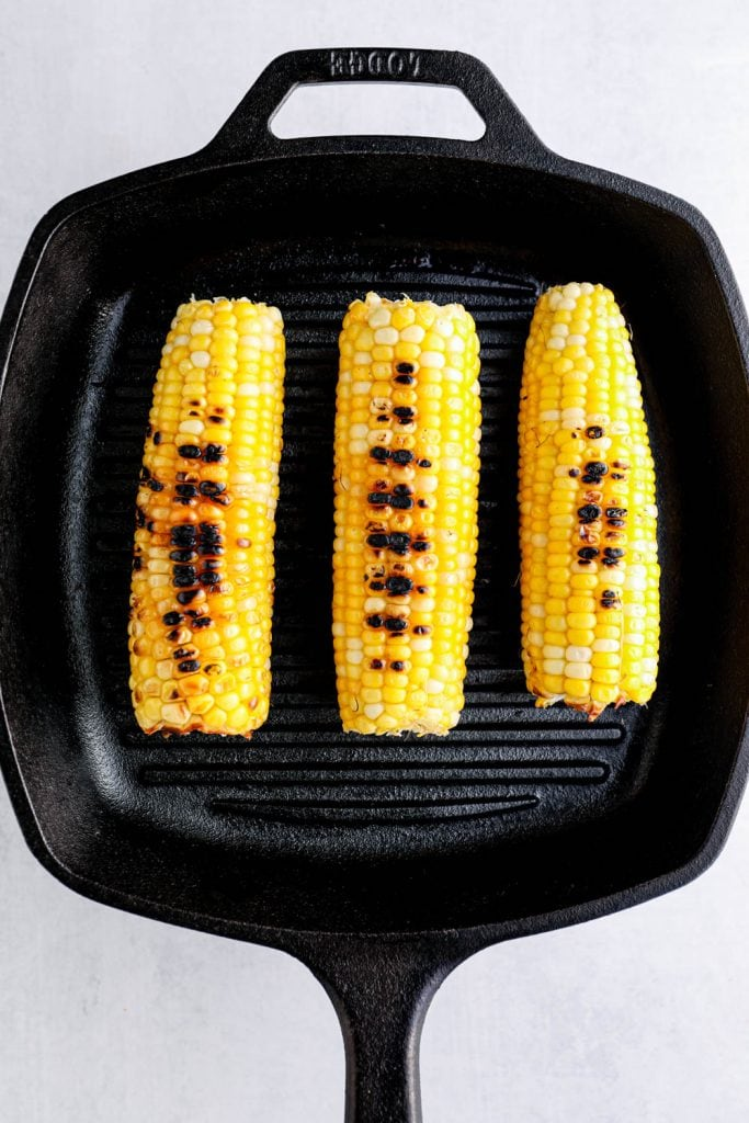 Corn grilling in a cast iron grill pan.